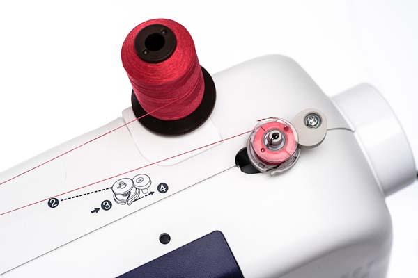 Sewing machine bobbin winder with a red thread
