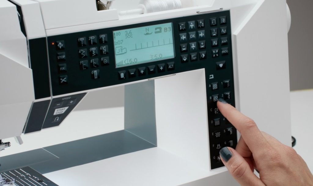 Person pressing buttons on a sewing machine panel