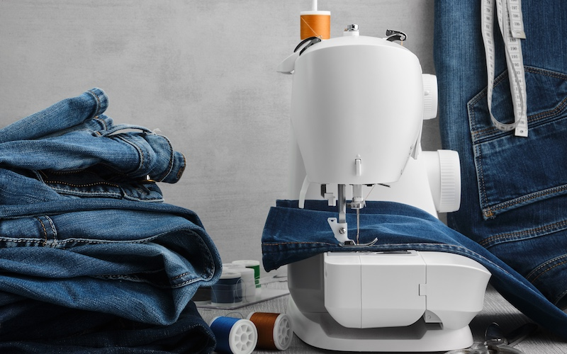 Denim jeans on a sewing machine