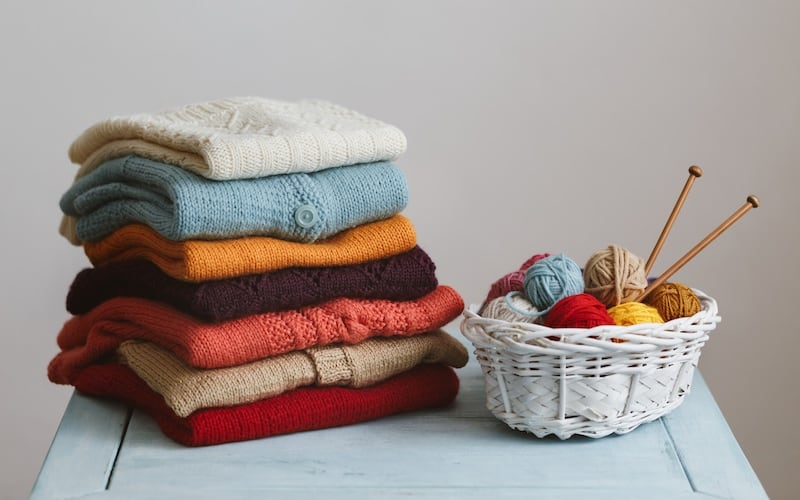 knitted garments and a basket with yarn on the table