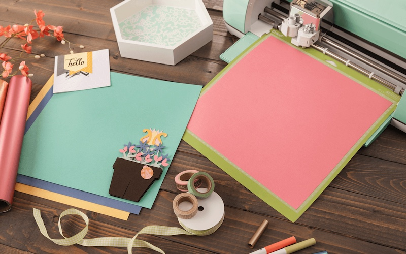 die cutting machine and craft supplies on a wooden table