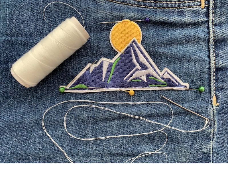 Patch pinned with denim fabric with white thread and a needle