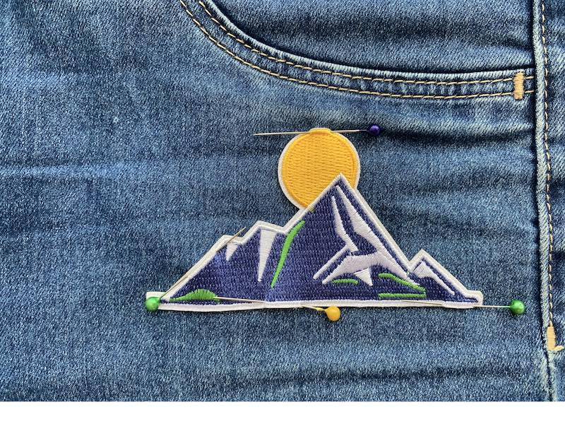 Patch pinned to the denim fabric with sewing pins