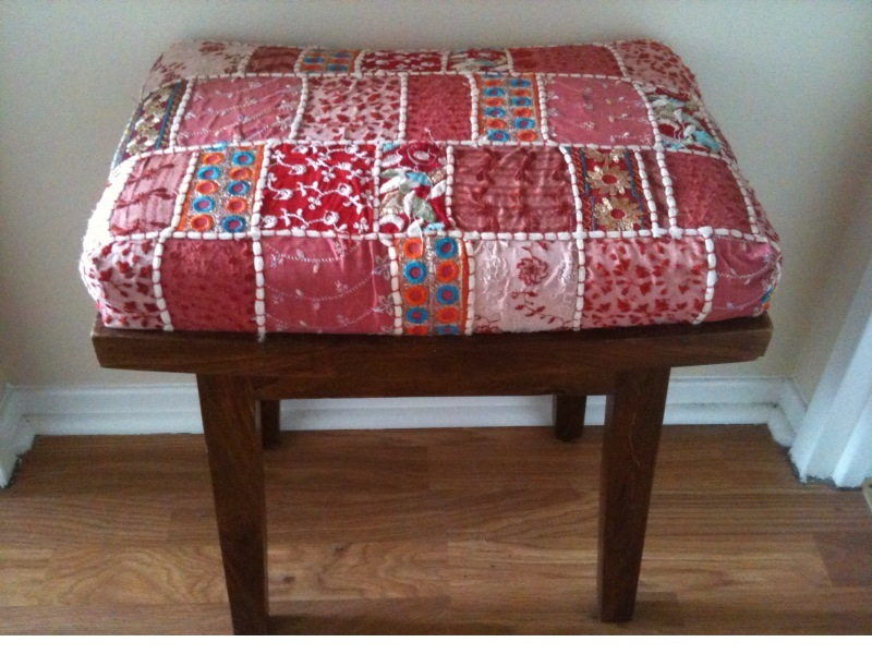A stool with a decorative quilt textile upholstery