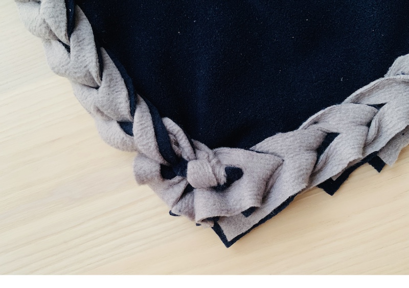 a fleece blanket with braided edges
