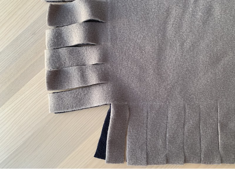 a piece of fleece fabric with fringes cut out on two sides