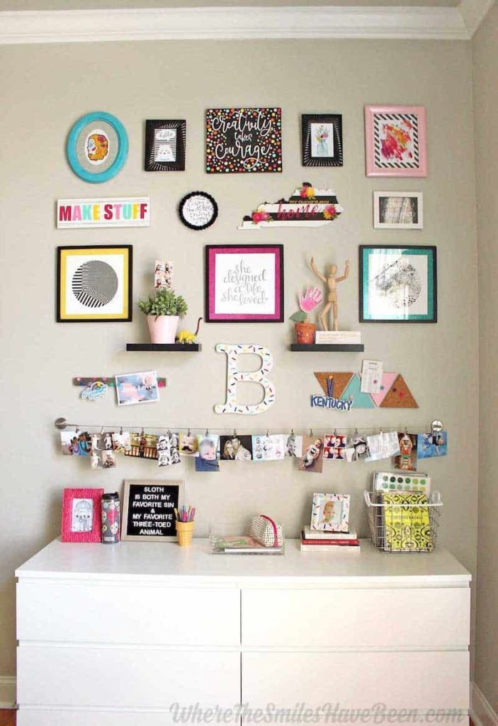 photos and illustrations hanging on the wall over a white dresser