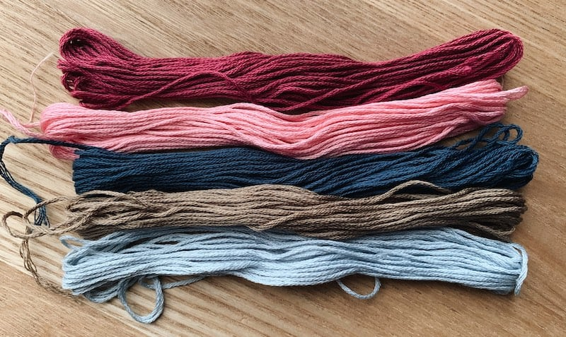 embroidery floss in different colors on a wooden table