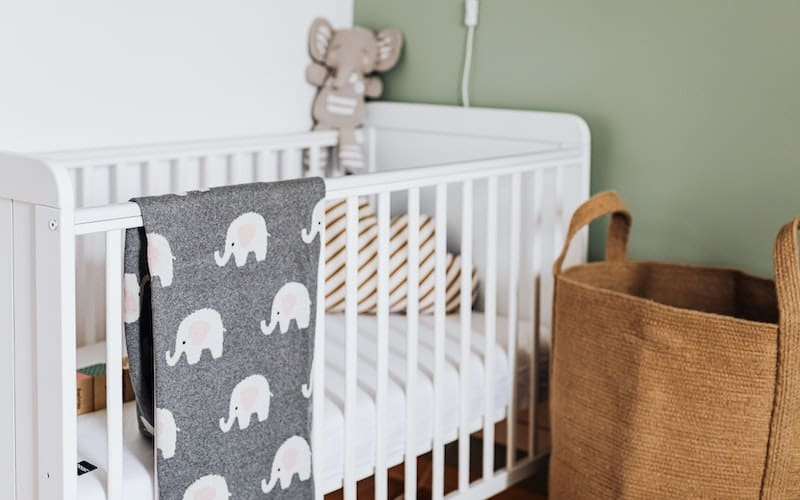 a baby blanket hanging on the side of a baby crib
