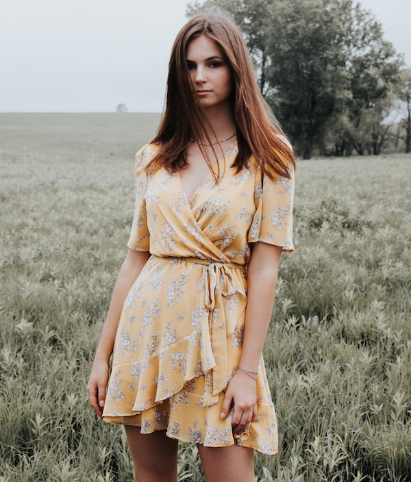 woman wearing a yellow floral printed wrap dress